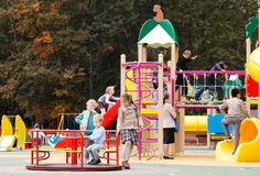 Kinder, die in einem Spielplatz im Freien spielen Lizenzfreie Stockfotografie