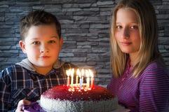 Kinder, die einen festlichen Kuchen mit zehn Kerzen halten Stockfoto