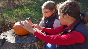 Kinder, die einen Kürbis schnitzen Stockfotografie
