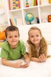 Kinder, die einen Musikspieler legt auf den Fußboden teilen stockfotografie