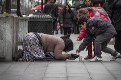 Kinder, die einer Bettlerdame helfen Stockfotos