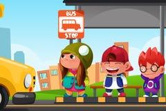Kinder, die an einer Bushaltestelle warten Stockbilder