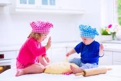 Kinder, die in einer weißen Küche backen stockfotos