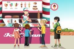 Kinder, die Eiscreme kaufen Stockfotos