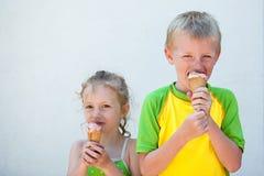 Kinder, die Eiscremekegel essen Stockfoto