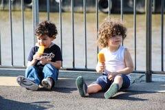 Kinder, die Eislutscher essen Stockfotos