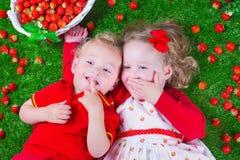 Kinder, die Erdbeere essen lizenzfreie stockbilder