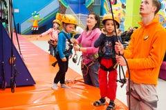 Kinder, die für das Klettern einer künstlichen Wand ausgerüstet werden lizenzfreie stockfotografie
