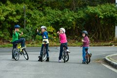 Kinder, die Fahrradsturzhelme tragen Stockbilder