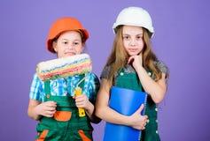 Kinder, die Farbenfarbe f?r ihren neuen Raum w?hlen Kinderm?dchen, die Erneuerung planen Kinderschwestern die ihre lassen Erneuer stockbild