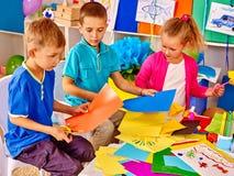 Kinder, die farbiges Papier auf Tabelle im Kindergarten halten lizenzfreie stockfotografie
