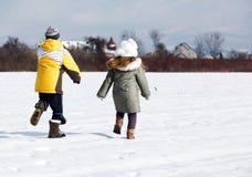 Kinder, die in Feld laufen Stockbilder