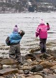 Kinder, die Felsen werfen Stockbild