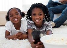 Kinder, die fernsehen und Knallmais essen Stockbilder