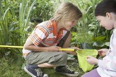 Kinder, die Fischernetz untersuchen Stockfoto