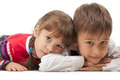 Kinder, die flach auf den Fußboden legen Stockbilder