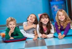 Kinder, die in Folge auf Boden im Kindergarten liegen stockbilder