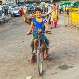 Kinder, die früh auf einem Fahrrad sitzen Lizenzfreie Stockfotografie