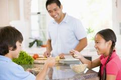 Kinder, die frühstücken, während Vati Nahrung zubereitet Lizenzfreie Stockfotos