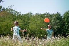 Kinder, die Frisbee spielen Stockfoto