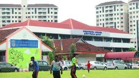 Kinder, die Fußball in einem Sportplatz spielen Jungen, die Fußball am Netz werfen stock footage