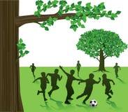 Kinder, die Fußball im Park spielen Lizenzfreies Stockbild