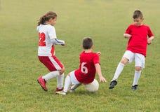 Kinder, die Fußball treten Stockfotos