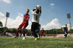 Kinder, die Fußballfußballspiel spielen Stockbild