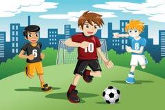 Kinder, die Fußball spielen Stockbilder