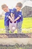 Kinder, die Garten wässern Lizenzfreies Stockbild
