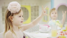 Kinder, die Geburtstag feiern und voll durch verzierte Tabelle der Nahrung sitzen stock footage