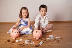 Kinder, die Geld im Sparschwein sammeln Lizenzfreie Stockbilder