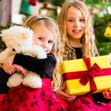 Kinder, die Geschenke auf Weihnachten empfangen Stockbild