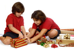 Kinder, die Geschenke einwickeln Lizenzfreie Stockfotos