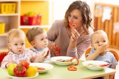 Kinder, die gesundes Lebensmittel im Kindergarten, Kindertagesstätte oder zu Hause essen lizenzfreies stockbild