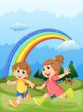 Kinder, die am Gipfel mit einem Regenbogen im Himmel spielen Stockbild