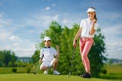 Kinder, die Golf spielen lizenzfreie stockbilder