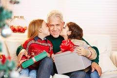 Kinder, die Großvater mit Geschenken auf Weihnachten küssen Lizenzfreie Stockfotos