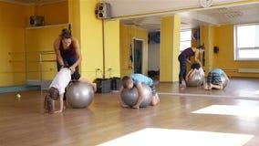 Kinder, die gymnastische Übungen mit geeigneten Bällen tun stock video
