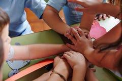 Kinder, die Hände in der Teamwork stapeln Stockbilder