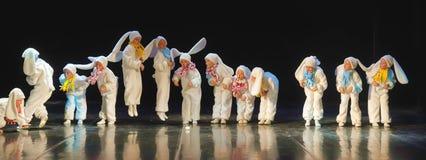 Kinder, die in Häschenkostüme tanzen Stockbild