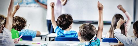 Kinder, die Hand im Klassenzimmer anheben lizenzfreie stockbilder