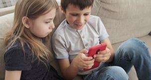 Kinder, die Handy auf Sofa verwenden stock footage
