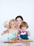 Kinder, die Heimarbeit mit ihrer Mutter mit Spindel tun Stockfotografie