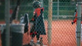 Kinder, die herum spielen, wie sie warten, um am Baseballspiel zu schlagen stock video footage