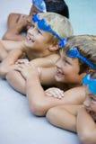 Kinder, die, hängend an der Seite des Swimmingpools lächeln Stockbild