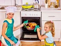 Kinder, die Huhn an der Küche kochen Stockbilder