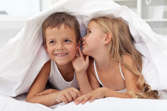 Kinder, die ihre Geheimnisse unter der Steppdecke teilen lizenzfreie stockbilder