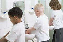 Kinder, die ihre Hände in einem Schulebadezimmer waschen Lizenzfreies Stockbild