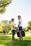 Kinder, die ihre Hände zurück schauen beim Halten eines Gepäcks halten Lizenzfreies Stockfoto